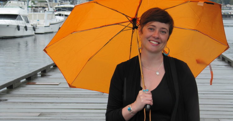 Heather Evans stands on a boat dock holding an orange umbrella.