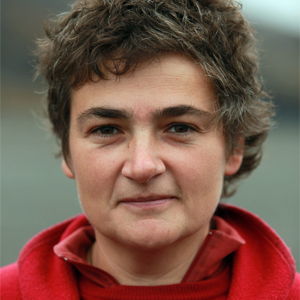 Dr. Fiamma Straneo, a brunette woman with close-cropped hair is wearing a red zip up sweater