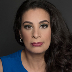 Headshot of comedian Maysoon Zayid, a brunette woman with long hair, gold earrings and red lips. She is wearing a sleeveless blue top.