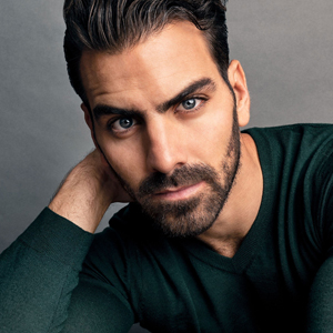 Headshot of Nyle DiMarco, a tan man with brown facial hair and head hair. he is wearing a green long sleeve sweater.