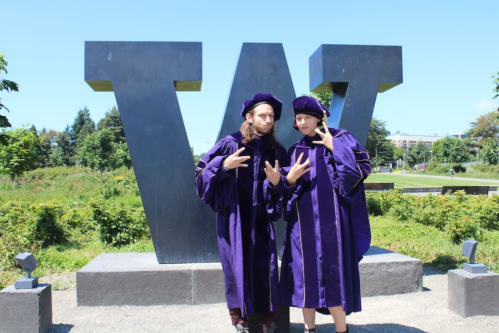 Ashley Ruba and James Clark stand in front of metal W sign outdoors in purple graduation robes