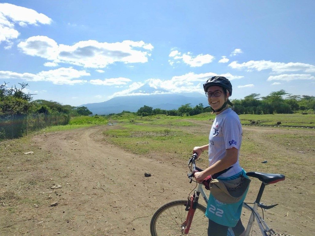 Photo of Kelsey Bilek on a bike with Mt Meru in the background