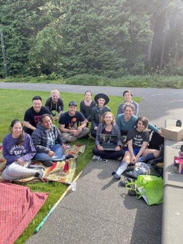 a group of 11 people sitting on picnic blankets outside, smiling for the camera.