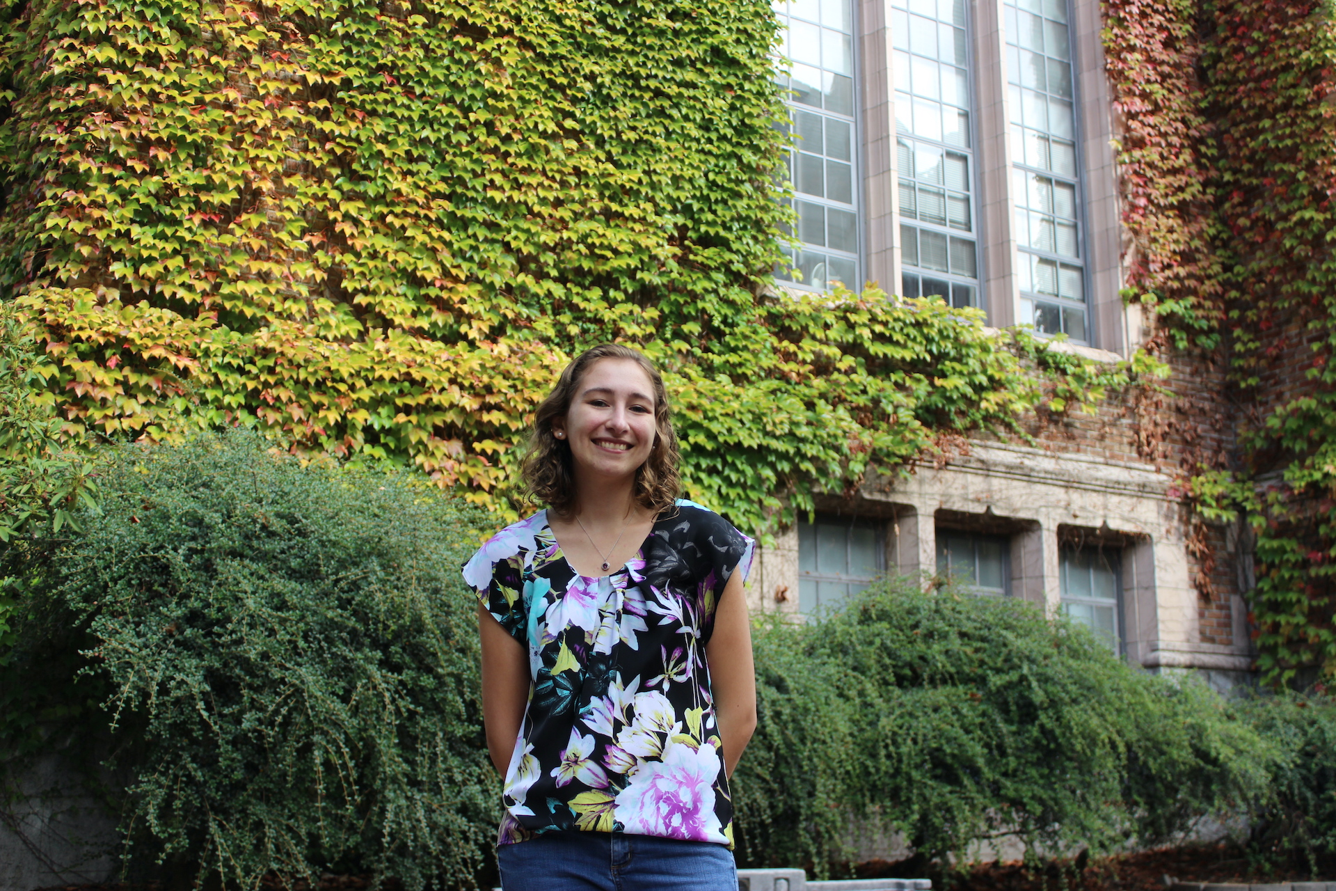 Kelly, a woman in her 20s, smiles as she stands in front of a brick building covered in green and yellow ivy.