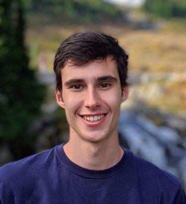 Headshot of Felix Schwock in front of blurred nature background.