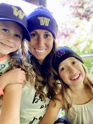 Perkins and her two daughters smile as they take a selfie. They all wear purple hats with a gold W.