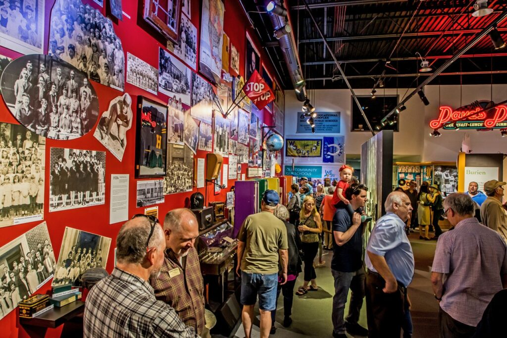 People gather inside museum. Historical posters adorn wall.