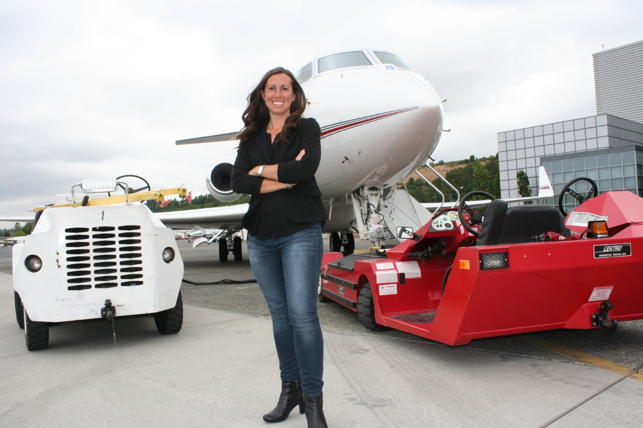 Kimberly Perkins smiles as she stands in front of an airplane with her arms crossed.