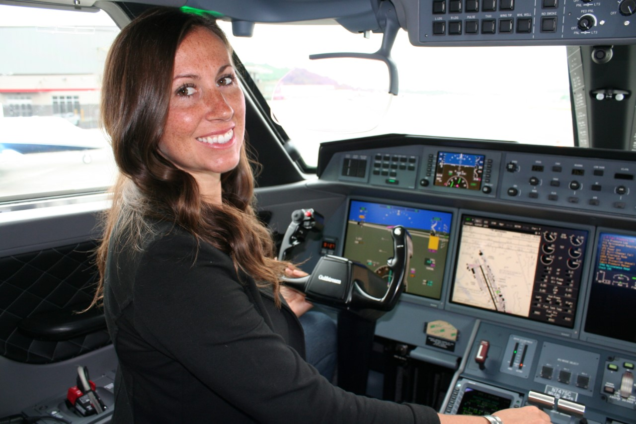 Kimberly Perkins smiles over her shoulder as she sits in the cockpit of an airplane with her hands on the controls.