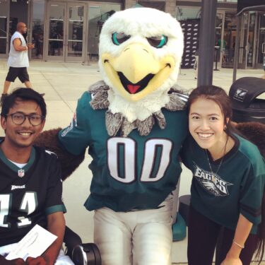 Ather Sharif and friend pose next to Eagles mascot outside stadium