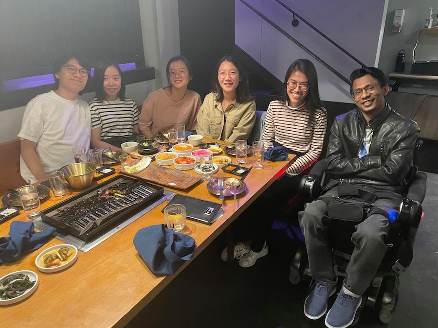 Ather sits with five friends around table with food on it at restaurant.